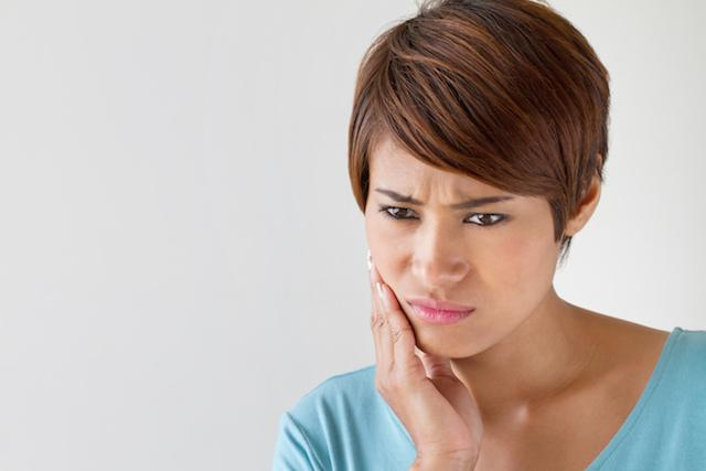 Woman holding jaw in pain | Dentist Duxbury MA