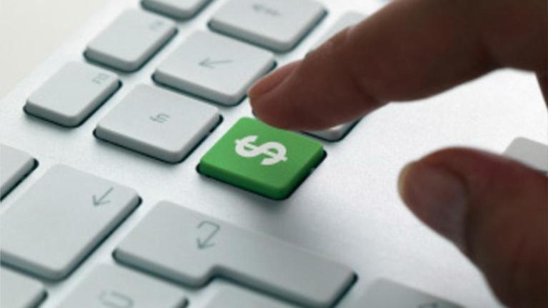 Person pressing keyboard with money sign on it